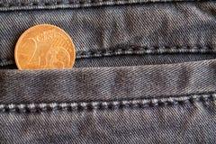 Euromynt med en valör av cent för euro 2 i facket av sliten blå grov bomullstvilljeans Arkivfoto