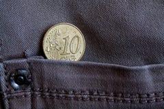 Euromynt med en valör av cent för euro 10 i facket av sliten grå grov bomullstvilljeans Arkivfoto