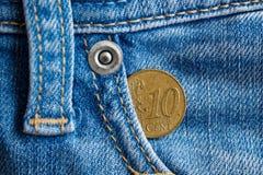 Euromynt med en valör av cent för euro tio i facket av sliten blå grov bomullstvilljeans för tappning Arkivbild