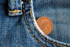 Euromynt med en valör av cent för euro två i facket av föråldrad blå grov bomullstvilljeans Arkivbilder