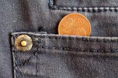 Euromynt med en valör av cent för euro två i facket av mörker - blå grov bomullstvilljeans Fotografering för Bildbyråer