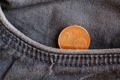 Euromynt med en valör av cent för euro två i facket av sliten blå grov bomullstvilljeans Royaltyfri Fotografi
