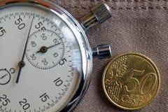 Euromynt med en valör av 50 den eurocent och stoppuren på den gamla beigea jeansbakgrunden - affärsbakgrund Arkivfoto
