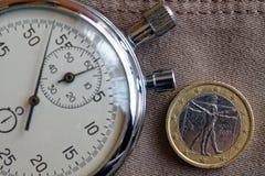 Euromynt med en valör av ett euro (tillbaka sida) och stoppuren på den gamla beigea jeansbakgrunden - affärsbakgrund Royaltyfria Foton