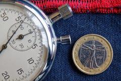 Euromynt med en valör av ett euro (tillbaka sida) och stoppuren på sliten blå grov bomullstvill med den röda bandbakgrunden - aff Royaltyfri Bild