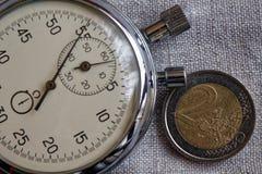 Euromynt med en valör av 2 euro och stoppur på den vita linnebakgrunden - affärsbakgrund Royaltyfri Foto