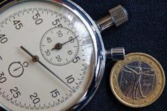 Euromynt med en valör av 1 euro (tillbaka sida) och stoppuren på den slitna svarta grov bomullstvillbakgrunden - affärsbakgrund Royaltyfri Bild