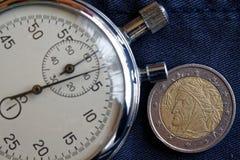 Euromynt med en valör av euro två (tillbaka sida) och stoppuren på den slitna jeansbakgrunden - affärsbakgrund Royaltyfri Foto