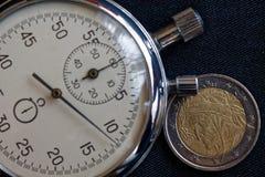 Euromynt med en valör av euro två (tillbaka sida) och stoppuren på den slitna svarta grov bomullstvillbakgrunden - affärsbakgrund Royaltyfri Bild