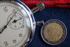 Euromynt med en valör av euro två (tillbaka sida) och stoppuren på sliten blå grov bomullstvill med den röda bandbakgrunden - aff Royaltyfri Foto