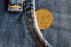 Euromynt med en valör av 10 eurocent i facket av blå föråldrad grov bomullstvilljeans Arkivfoto