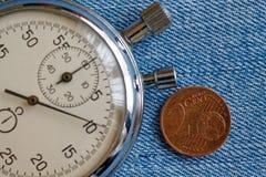 Euromynt med en valör av 2 eurocent och stoppur på den blåa grov bomullstvillbakgrunden - affärsbakgrund Royaltyfri Bild