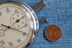 Euromynt med en valör av en eurocent och stoppur på den blåa grov bomullstvillbakgrunden - affärsbakgrund Arkivbild