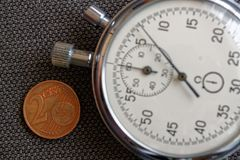 Euromynt med en valör av 2 eurocent och stoppur på den bruna grov bomullstvillbakgrunden - affärsbakgrund Arkivfoto