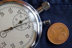 Euromynt med en valör av 5 eurocent och stoppur på den föråldrade blåa grov bomullstvillbakgrunden - affärsbakgrund Arkivbild