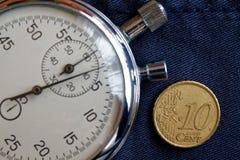 Euromynt med en valör av 10 eurocent och stoppur på den föråldrade blåa grov bomullstvillbakgrunden - affärsbakgrund Arkivfoto
