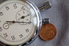 Euromynt med en valör av 2 eurocent och stoppur på den gråa grov bomullstvillbakgrunden - affärsbakgrund Royaltyfria Bilder