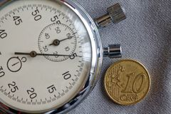 Euromynt med en valör av 10 eurocent och stoppur på den gråa grov bomullstvillbakgrunden - affärsbakgrund Royaltyfri Foto