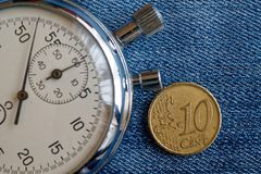 Euromynt med en valör av 10 eurocent och stoppur på den slitna blåa grov bomullstvillbakgrunden - affärsbakgrund Arkivbilder