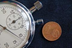 Euromynt med en valör av 2 eurocent och stoppur på den svarta grov bomullstvillbakgrunden - affärsbakgrund Arkivbild