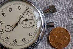 Euromynt med en valör av 5 eurocent och stoppur på den vita linnebakgrunden - affärsbakgrund Royaltyfri Foto