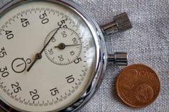Euromynt med en valör av 2 eurocent och stoppur på den vita linnebakgrunden - affärsbakgrund Arkivfoto