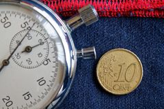 Euromynt med en valör av 10 eurocent och stoppur på sliten jeans med den röda bandbakgrunden - affärsbakgrund Arkivfoto