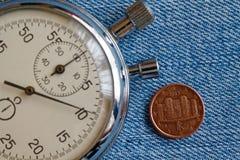 Euromynt med en valör av 1 eurocent (tillbaka sida) och stoppuren på den blåa grov bomullstvillbakgrunden - affärsbakgrund Arkivbilder