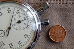 Euromynt med en valör av en eurocent (tillbaka sida) och stoppuren på den gamla beigea jeansbakgrunden - affärsbakgrund Royaltyfri Fotografi