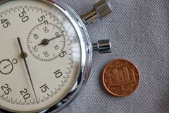 Euromynt med en valör av 1 eurocent (tillbaka sida) och stoppuren på den gråa grov bomullstvillbakgrunden - affärsbakgrund Royaltyfri Fotografi