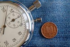 Euromynt med en valör av en eurocent (tillbaka sida) och stoppuren på den slitna blåa grov bomullstvillbakgrunden - affärsbakgrun Royaltyfri Bild