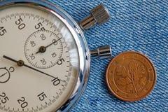Euromynt med en valör av fem eurocent (tillbaka sida) och stoppuren på den blåa grov bomullstvillbakgrunden - affärsbakgrund Arkivbild