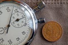 Euromynt med en valör av fem eurocent (tillbaka sida) och stoppuren på den gamla beigea jeansbakgrunden - affärsbakgrund Arkivfoton