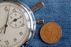 Euromynt med en valör av fem eurocent (tillbaka sida) och stoppuren på den slitna blåa grov bomullstvillbakgrunden - affärsbakgru Royaltyfria Foton