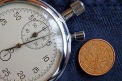Euromynt med en valör av fem eurocent (tillbaka sida) och stoppuren på den slitna jeansbakgrunden - affärsbakgrund Arkivfoton