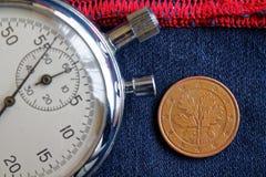 Euromynt med en valör av fem eurocent (tillbaka sida) och stoppuren på sliten blå grov bomullstvill med den röda bandbakgrunden - Royaltyfri Fotografi