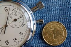 Euromynt med en valör av femtio eurocent (tillbaka sida) och stoppuren på den slitna blåa grov bomullstvillbakgrunden - affärsbak Royaltyfri Foto