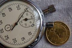 Euromynt med en valör av femtio eurocent (tillbaka sida) och stoppuren på den vita linbakgrunden - affärsbakgrund Arkivbild