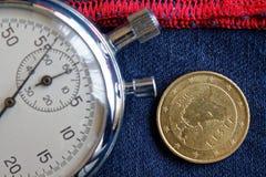 Euromynt med en valör av femtio eurocent (tillbaka sida) och stoppuren på sliten blå grov bomullstvill med den röda bandbakgrunde Royaltyfria Bilder