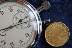 Euromynt med en valör av fifityeurocent (tillbaka sida) och stoppuren på den slitna jeansbakgrunden - affärsbakgrund Arkivfoton