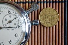 Euromynt med en valör av tio eurocent och stoppur på trätabellen - tillbaka sida Arkivbild