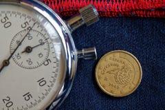 Euromynt med en valör av tio eurocent (tillbaka sida) och stoppuren på sliten blå grov bomullstvill med den röda bandbakgrunden - Fotografering för Bildbyråer