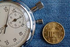 Euromynt med en valör av tjugo eurocent (tillbaka sida) och stoppuren på den slitna blåa grov bomullstvillbakgrunden - affärsbakg Royaltyfri Fotografi