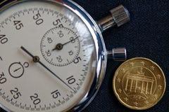 Euromynt med en valör av tjugo eurocent (tillbaka sida) och stoppuren på den slitna svarta grov bomullstvillbakgrunden - affärsba Arkivfoto