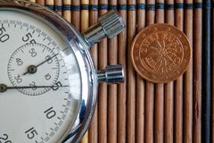 Euromynt med en valör av två eurocent och stoppur på trätabellen - tillbaka sida Arkivfoto