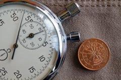 Euromynt med en valör av två eurocent (tillbaka sida) och stoppuren på den gamla beigea jeansbakgrunden - affärsbakgrund Fotografering för Bildbyråer