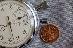 Euromynt med en valör av två eurocent (tillbaka sida) och stoppuren på den gråa grov bomullstvillbakgrunden - affärsbakgrund Royaltyfri Fotografi