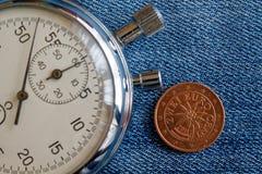 Euromynt med en valör av två eurocent (tillbaka sida) och stoppuren på den slitna blåa grov bomullstvillbakgrunden - affärsbakgru Royaltyfria Bilder