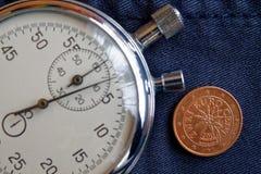 Euromynt med en valör av två eurocent (tillbaka sida) och stoppuren på den slitna jeansbakgrunden - affärsbakgrund Royaltyfria Bilder
