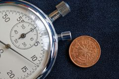 Euromynt med en valör av två eurocent (tillbaka sida) och stoppuren på den slitna svarta grov bomullstvillbakgrunden - affärsbakg Royaltyfria Foton